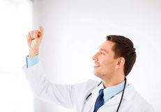 Young doctor holding something imaginary Royalty Free Stock Photos
