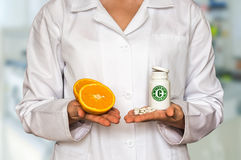 Young doctor holding two halves of orange and bottle of pills wi. Young doctor holding two halves of fresh orange and bottle of pills with vitamin C and compare royalty free stock images