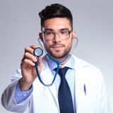 Young doctor holding up stethoscope Stock Photos