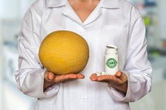 Young doctor holding yellow melon and bottle of pills with vitam Stock Photos