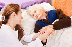 Young doctor holds the elderly woman hands royalty free stock image