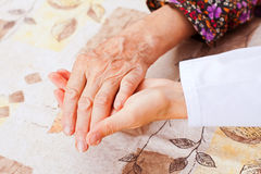 Young doctor holds the elderly woman hands Royalty Free Stock Photo