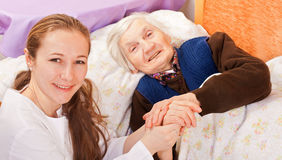 Young doctor holds the elderly woman hands stock image