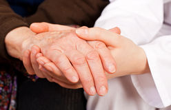 Young doctor holds the elderly woman hands Royalty Free Stock Photos