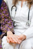 Young doctor holds the lady's hands. Young doctor holds the old lady's hands Royalty Free Stock Photos