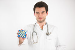 Young doctor holds tablets. Young male doctor, on white background, wearing white coat, holds colorful tablets Royalty Free Stock Image