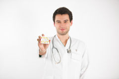Young doctor holds tablets. Young male doctor, on white background, wearing white coat, holds colorful tablets Royalty Free Stock Images