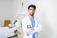Young doctor at hospital bedroom with sick patient lying in bed Stock Photography