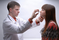 Young doctor inspecting patient's nose Royalty Free Stock Photos