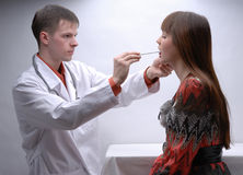 Young doctor inspecting patient's throat Stock Photos