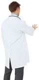 Young doctor in lab coat gesturing. On white background Stock Photos