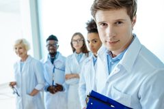 Young doctor in lab coat holding clipboard with group of young doctors in lab coats standing. Behind him stock photos