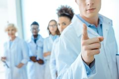 Young doctor in lab coat pointing his finger with group of young doctors in lab coats standing. Behind him royalty free stock images