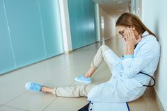 Young doctor in a lab coat sitting on a floor in hospital corridor and rubbing royalty free stock photography