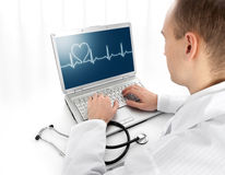 Young doctor with laptop. Rear view of a young doctor with laptop Royalty Free Stock Photos