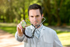 Young doctor listening with stethoscope. On the green park background Stock Image