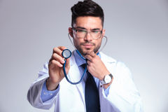 Young doctor listens concentrated at stethoscope Royalty Free Stock Photo
