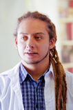 Young doctor with long dread locks posing for camera, clinic in background, medical concept.  Stock Images