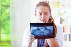 Young doctor with long dread locks posing for camera, holding up x ray image staring at it, clinic in background. Medical concept Stock Photos