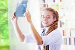 Young doctor with long dread locks posing for camera, holding up x ray image staring at it, clinic in background. Medical concept Royalty Free Stock Photo