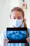 Young doctor with long dread locks posing for camera, holding up x ray image staring at it, wearing facial mask, clinic. In background, medical concept Stock Photo