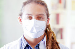 Young doctor with long dread locks posing for camera, wearing facial mask covering mouth, clinic in background, medical. Concept Stock Photography