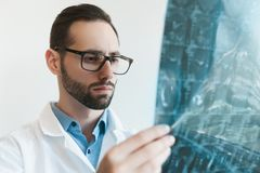 Young doctor looking at Magnetic resonance imaging shot of knee-joint. meniscus injury stock image