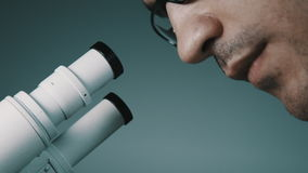 Young doctor looking through the microscope stock footage