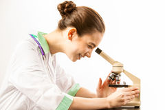 Young doctor looking into a microscope Royalty Free Stock Photos