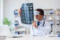 The young doctor looking at mri scan through vr glasses. Young doctor looking at MRI scan through VR glasses Royalty Free Stock Photography