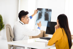 Young doctor looking at patient's x-ray film Royalty Free Stock Images