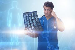 The young doctor looking at x-ray image in mhealth concept. Young doctor looking at x-ray image in mhealth concept royalty free stock photo