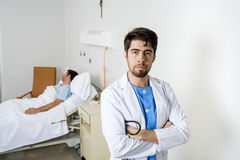 Young doctor looking serious worried corporate portrait at hospital bedroom with sick patient stock photos