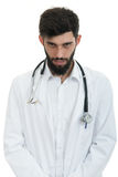 Young doctor man with stethoscope looking serious.  Royalty Free Stock Image