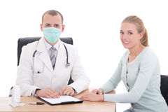 Young doctor in mask and female patient sitting isolated on whit Royalty Free Stock Photos