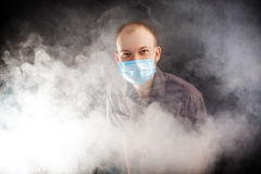 Young doctor in a mask in smoke. Young doctor in a mask in the smoke Royalty Free Stock Photos