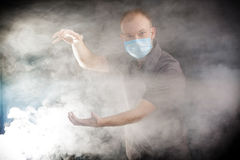 Young doctor in a mask in smoke. Young doctor in a mask in the smoke Stock Images