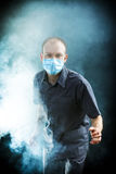 Young doctor in a mask in smoke. Young doctor in a mask in the smoke Royalty Free Stock Photography