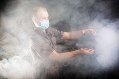 Young doctor in a mask in smoke. Young doctor in a mask in the smoke Stock Photos