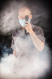 Young doctor in a mask in smoke. Young doctor in a mask in the smoke Stock Image