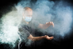 Young doctor in a mask in smoke. Young doctor in a mask in the smoke Royalty Free Stock Photo