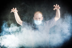 Young doctor in a mask in smoke. Young doctor in a mask in the smoke Stock Photography