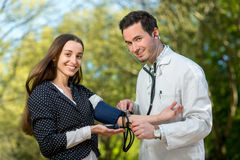 Young doctor measuring pressure to young lady in the park. Stock Images