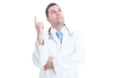 Young doctor or medic looking up and having great idea Royalty Free Stock Image