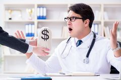 The young doctor in medical insurance fraud concept. Young doctor in medical insurance fraud concept Stock Photo