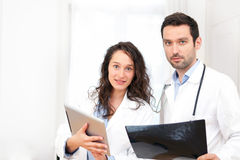 Young doctor and nurse analysing radiography Royalty Free Stock Photos