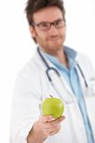 Young doctor offering green apple. Smiling Royalty Free Stock Photos