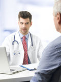 Young doctor with patient. Portrait of young doctor sitting at desk with elderly patient while check up and write diagnosis Royalty Free Stock Photography