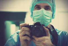 Portrait of a medical photographer. Young doctor photographing the medical procedures during surgery Stock Photography