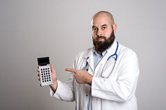 Young doctor pointing to pocket calculator Royalty Free Stock Image
